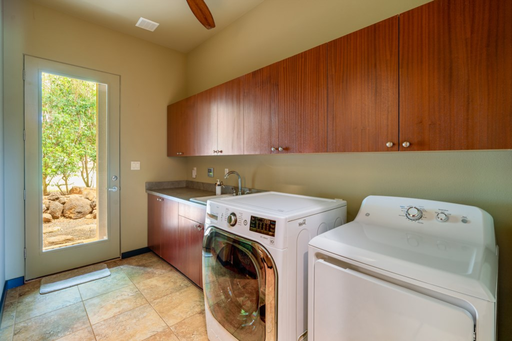 Spacious laundry room equipped with sink and cabinet space for storage