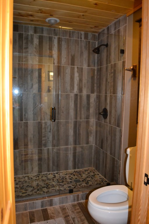 Convenient tiled walk-in shower with glass doors.