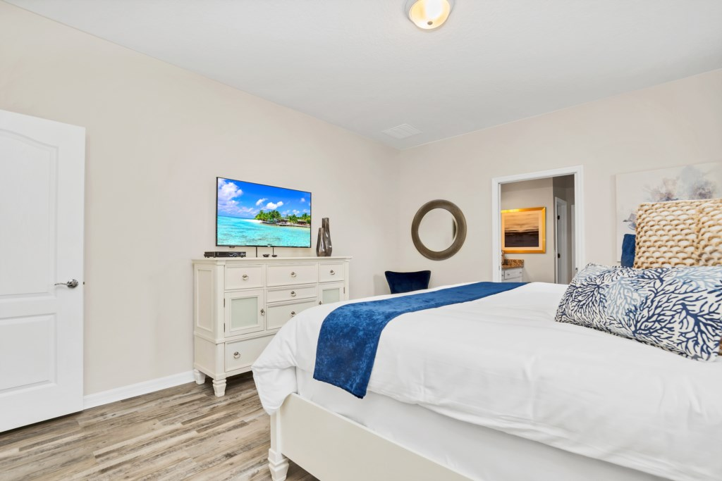 View 2 of stunning king bed with flat screen TV and access to patio