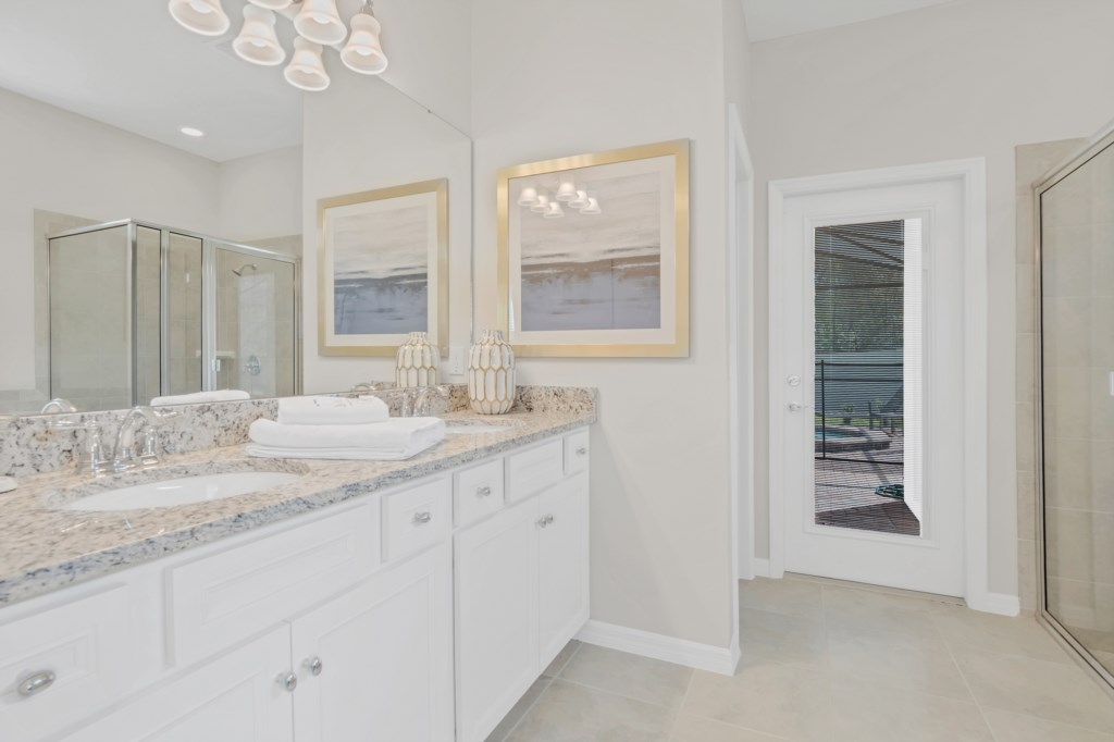 Stunning bathroom with tub, glass shower, and access to patio