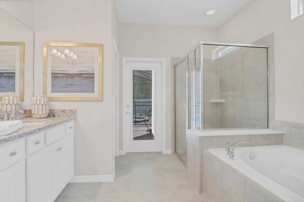 View 2 of stunning bathroom with tub, glass shower, and access to patio