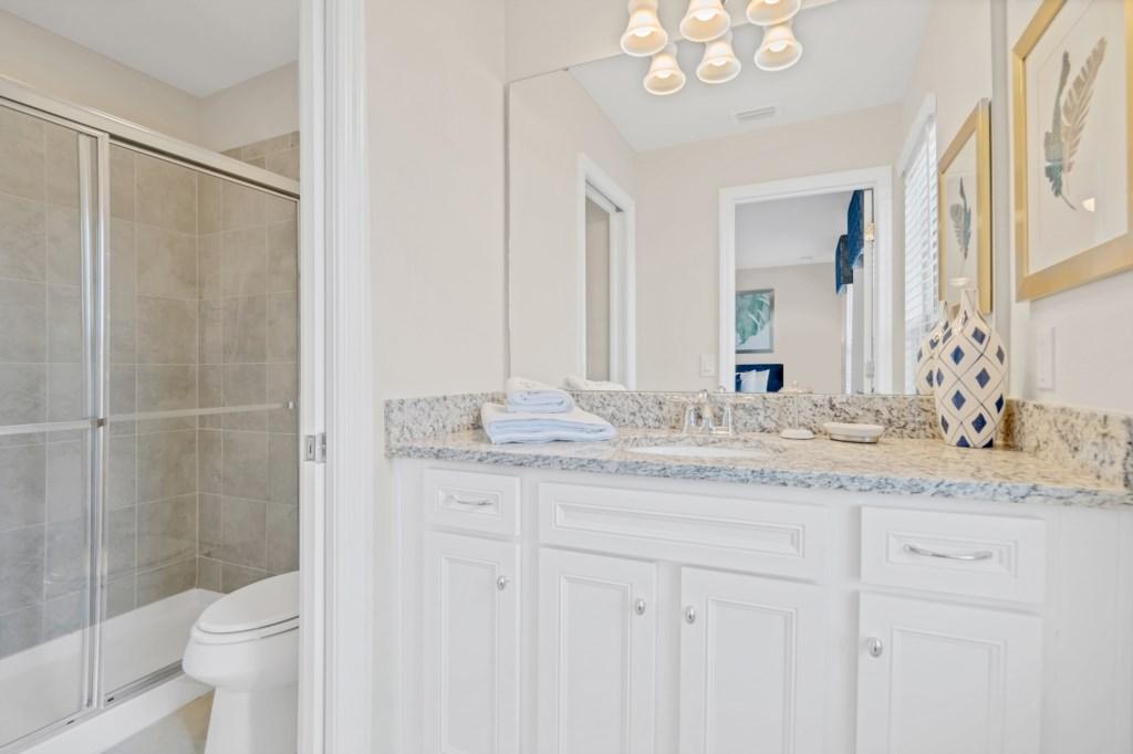 Classy single sink vanity with sliding glass shower