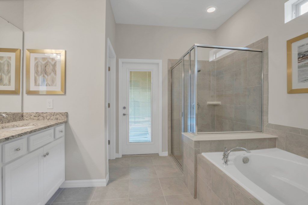 Stunning bathroom with tub, glass shower and access to patio