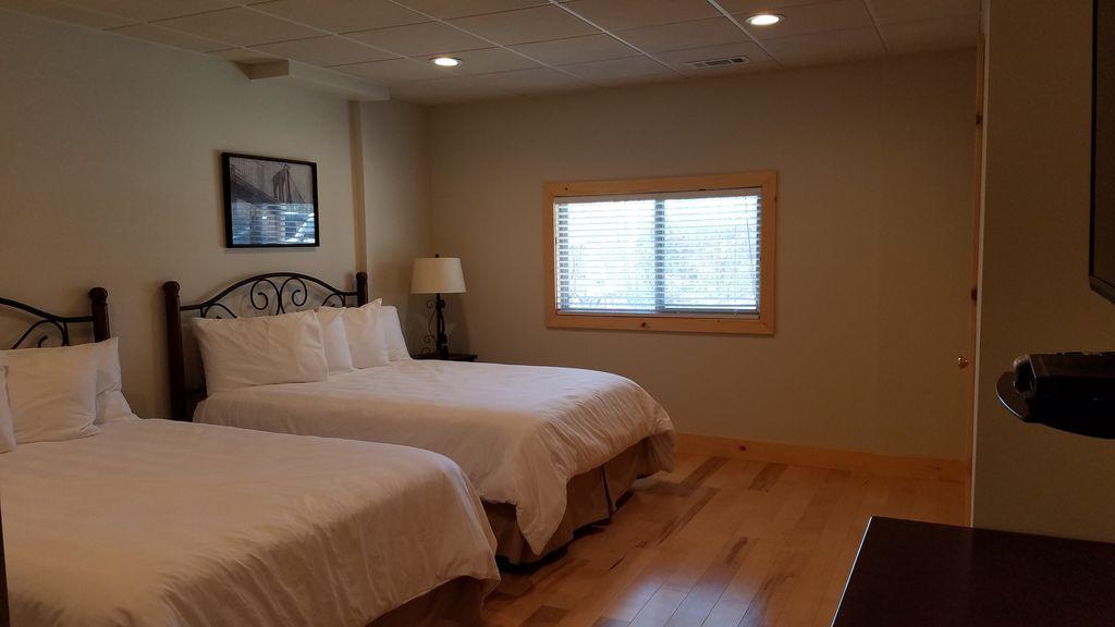 Basement Double Queen bedroom #5 with luxury bedding and 40 inch TV