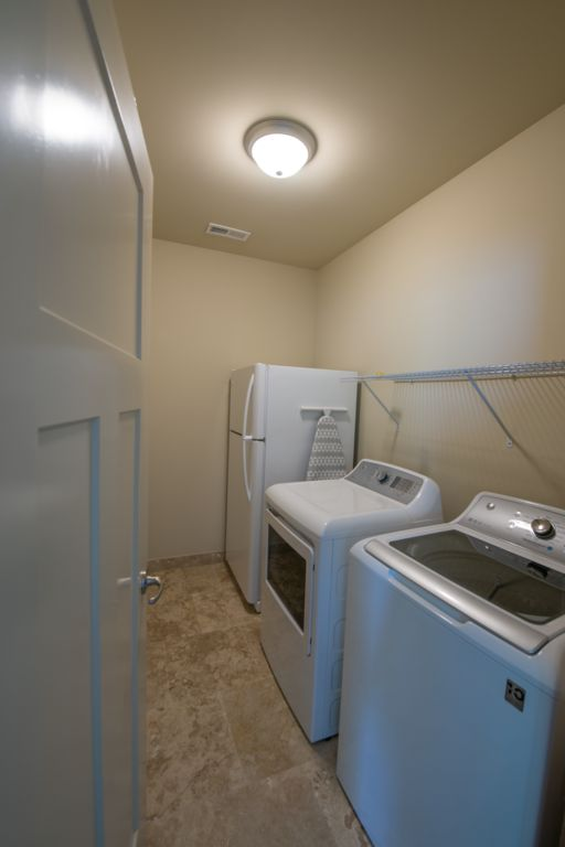 Laundry room with a full size refrigerator, washer and dryer. Plus Iron and ironing board