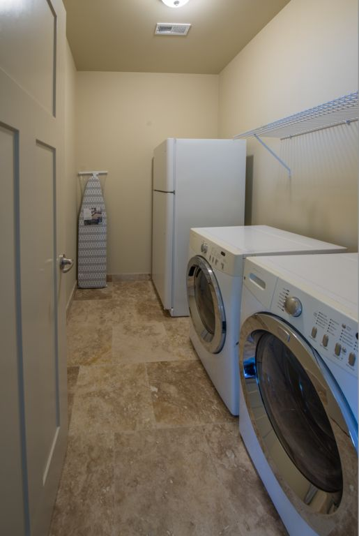 Laundry room with additional full size refrigerator. Also with Iron and ironing board.