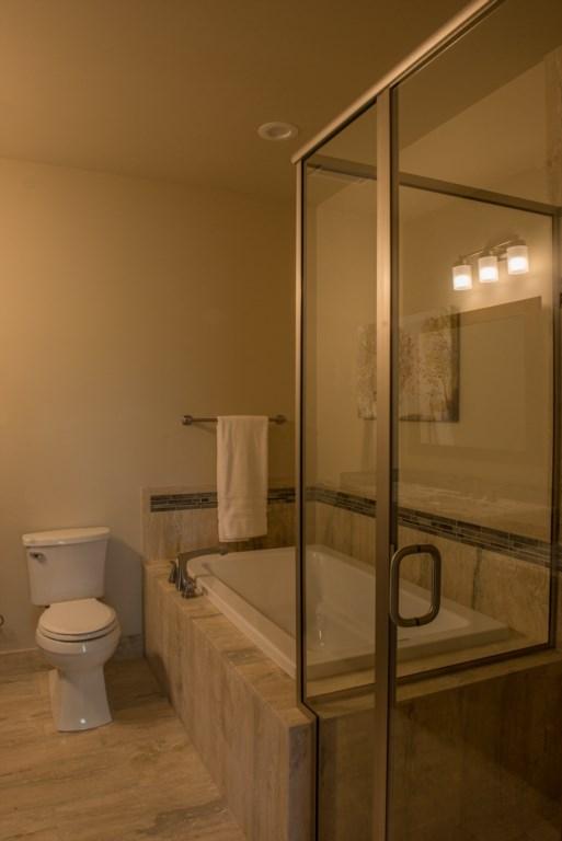 Master bath #1 features a custom natural stone walk-in shower and soaking tub. Relax. Soak. Unwind.