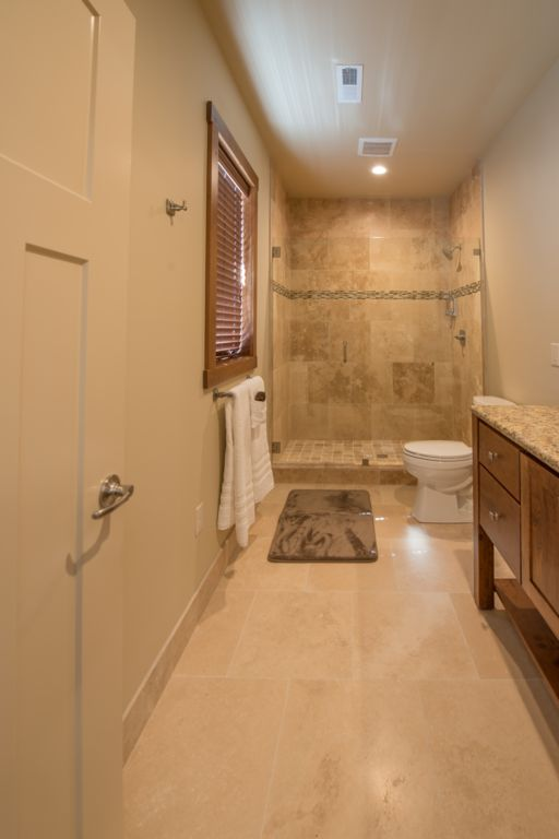 Mater bath #2 featuring a custom natural stone walk-in shower and double vanity.