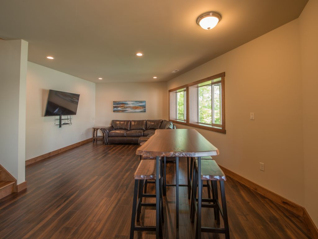Unwind in your open family great room featuring a 60 inch TV with panoramic views from every window