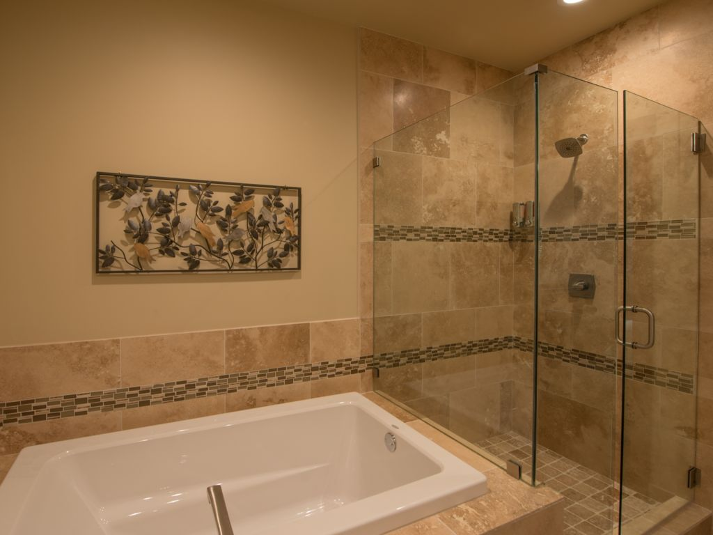Master bath #1 features a custom natural stone walk-in shower and soaking tub.