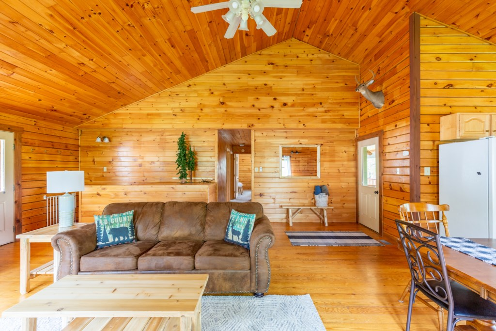 A spacious living room space equipped with a couch, ceiling fan, and chairs for ultimate relaxation.