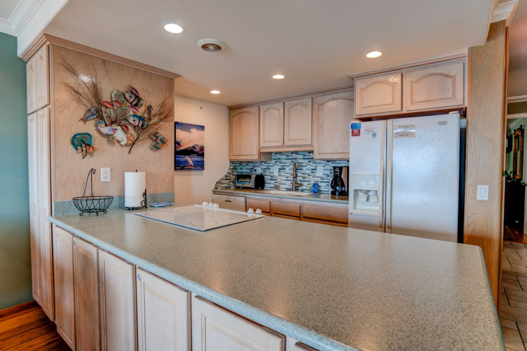 Fully equipped kitchen with custom cabinets, bright lighting, and updated appliances.
