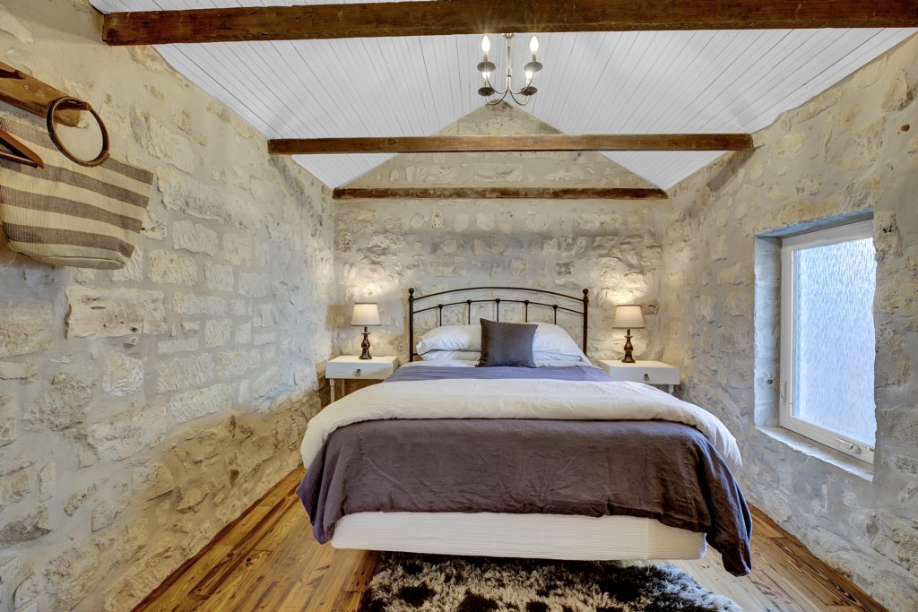 Remodeled and gorgeous bedrooms throughout the home feature traditional stone walls and beautiful wooden beams above!