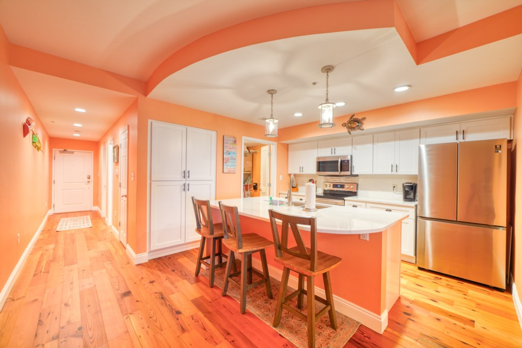 Chery hardwood floors and stone countertops with stainless appliances make this kitchen luxe