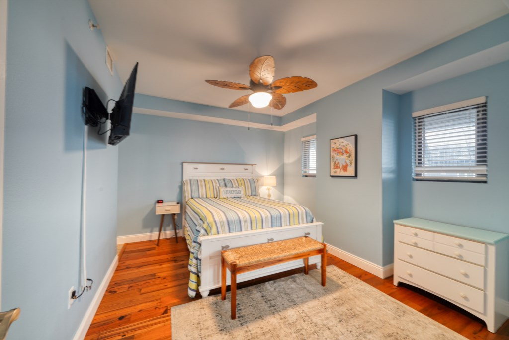 Queen master bedroom with balcony access, flay screen television, and attached bath