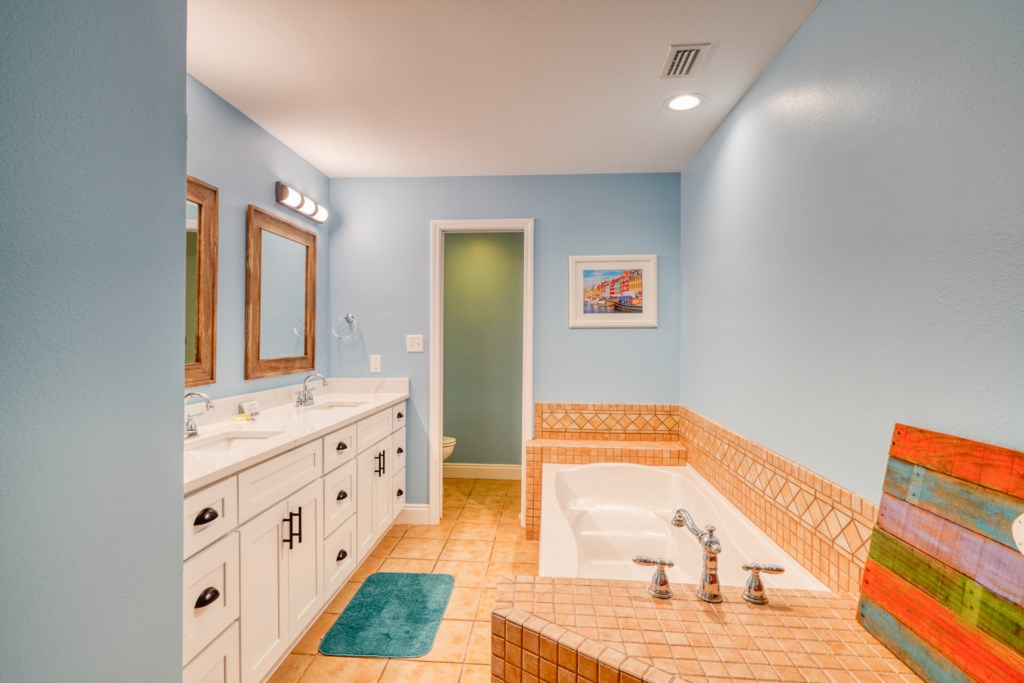 Master bathroom with soaking tub, double vanity, and stand along shower