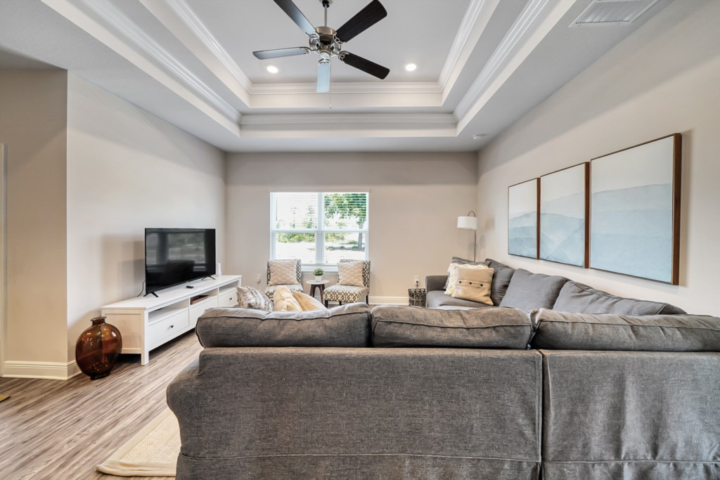 The living room provides a large sectional with comfortable seating, Roku tv, ceiling fan, and decorative tray ceilings