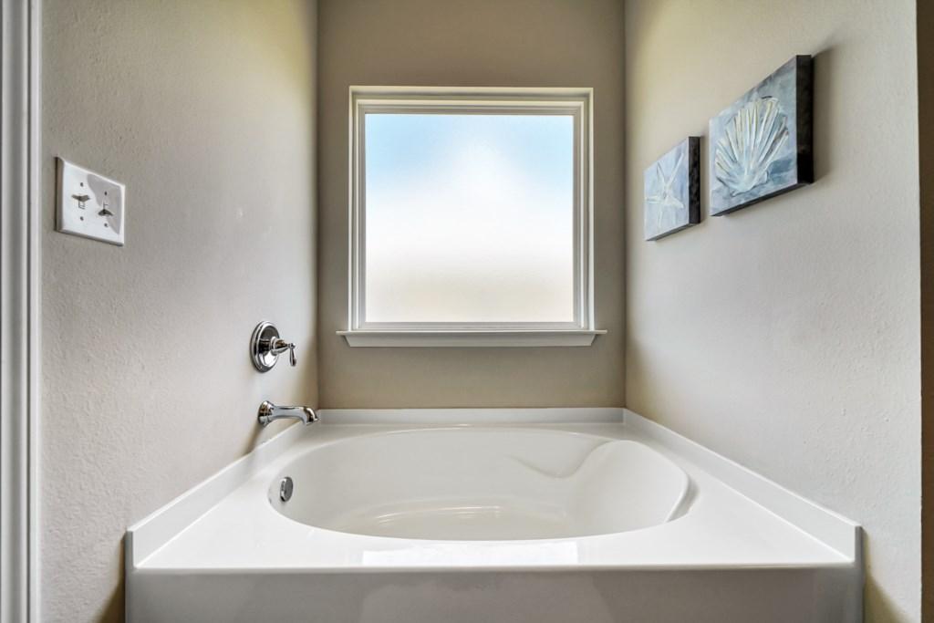 Large soaking tub with beautiful natural light