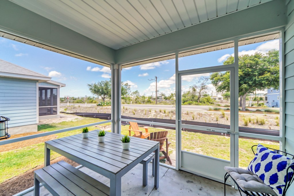 Screened in porch with seating for 5 and an additional seating for 2 via Adirondack chairs