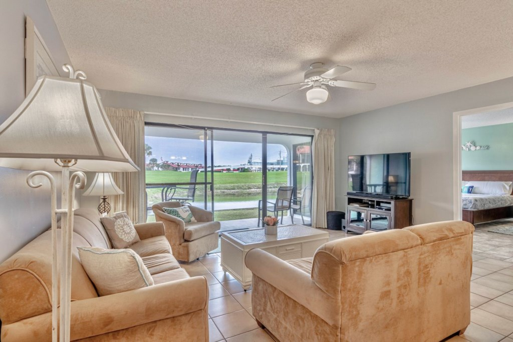 Large living room & patio which overlooks the golf course and one of the small lakes on property.