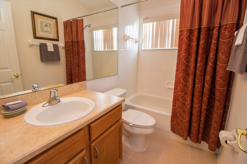 21-The queen bedroom ensuite has a shower over the bath and single sink.jpg