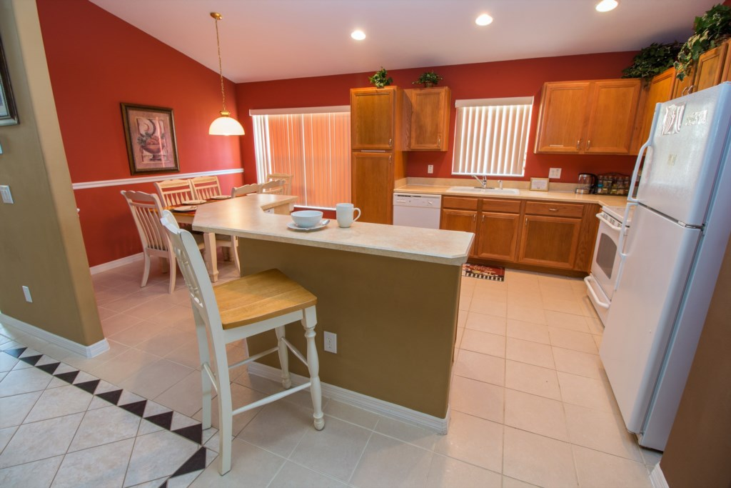 5-The kitchen has a tuscan feel with white cabinets and bar stool seating for one.jpg
