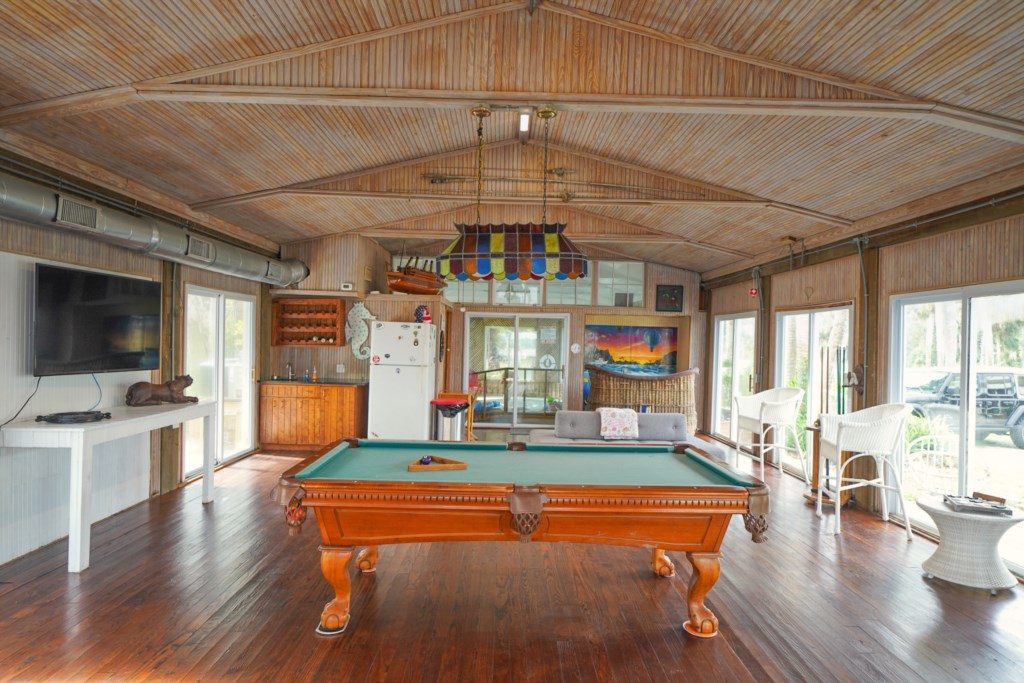 Game room with pool table and flat screen television, board games, and dry bar