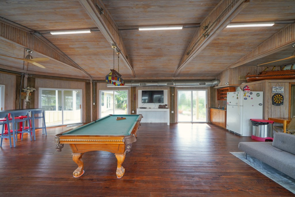 Game room with pool table, flat screen television, and half bath