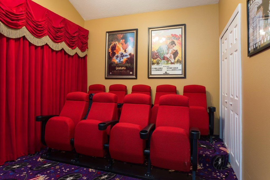 The home theater features tiered theater-style seating for nine