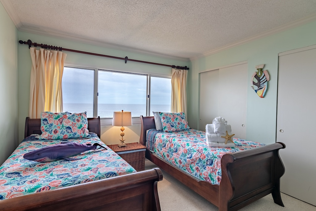 Bedroom 2 offers 2 twin sleigh beds with a view of the Gulf
