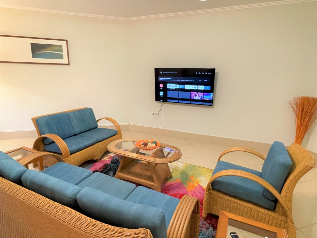 Spacious living room with large smart tv,ceiling fan and air conditioner