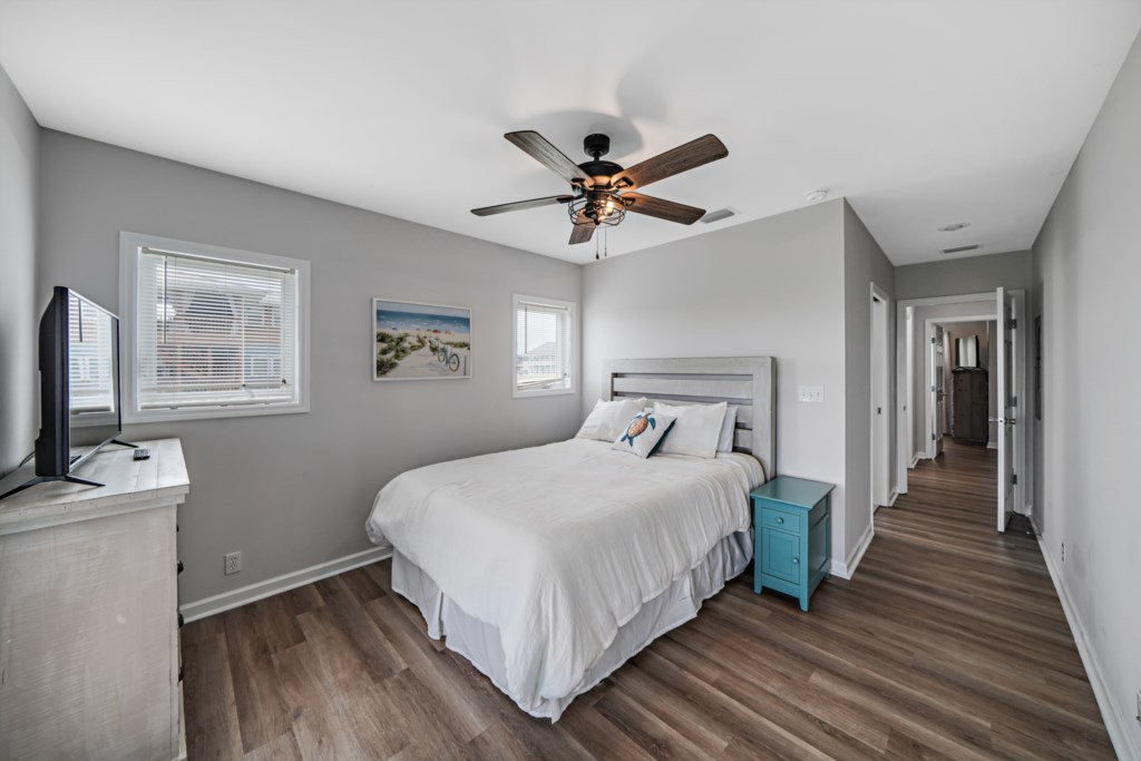 Queen bedroom with balcony access, ceiling fan, and flat screen television