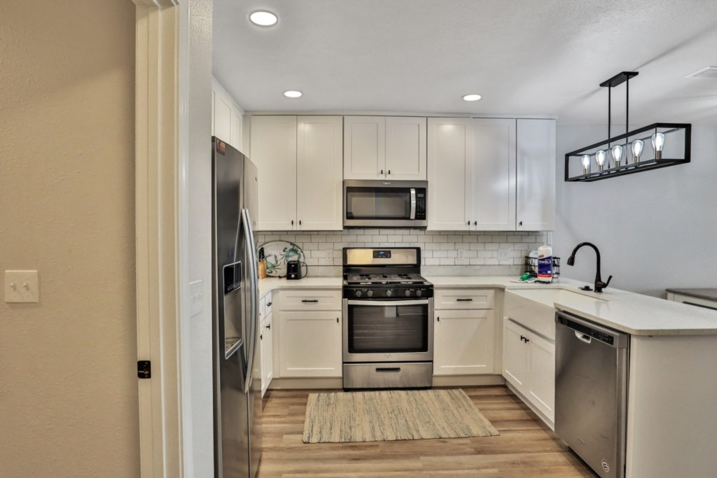 The kitchen is fully stocked with all dishes and utensils as well as a starter supply of amenities