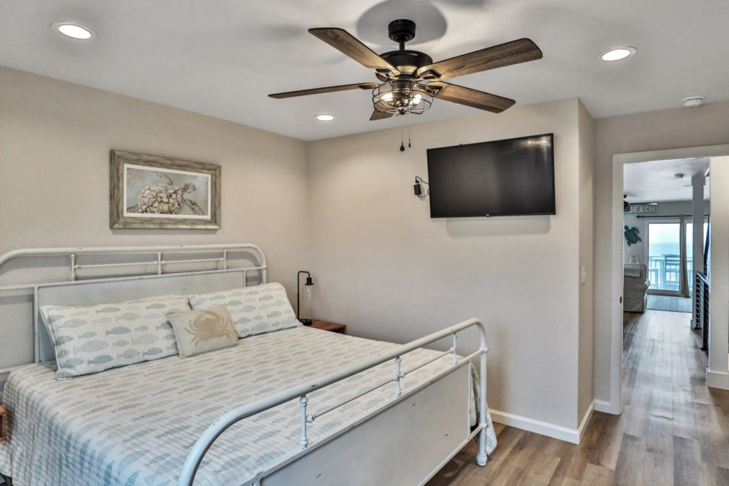 King guest room with ceiling fan, closet access, flat screen tv, and half bath