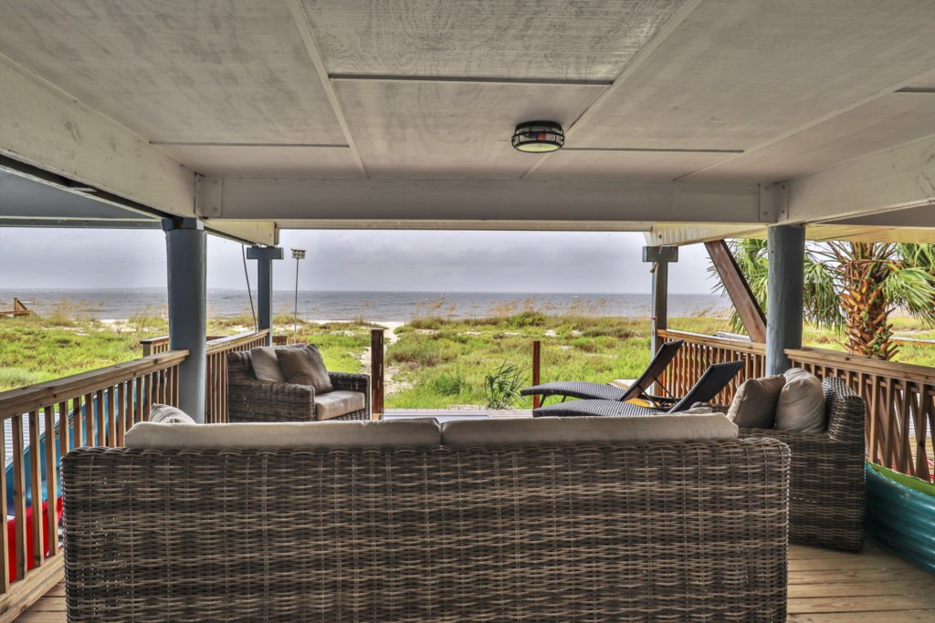 Covered lanai with outdoor seating and charcoal grill... literally ON THE BEACH