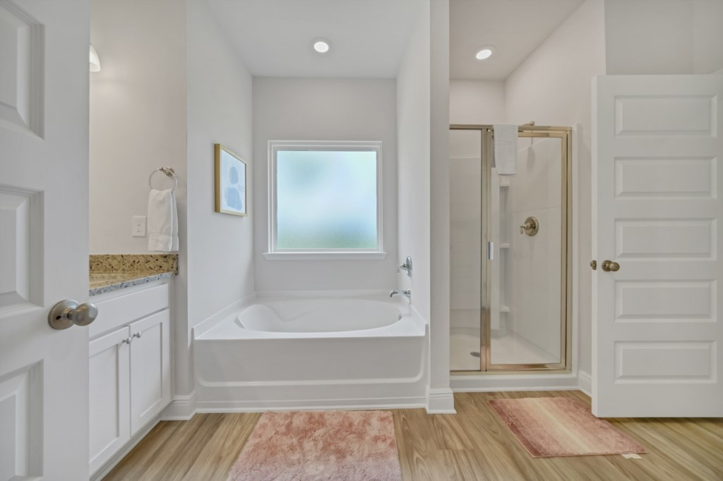 Luxurious bathroom with soaking tub graced by natural light and large walk-in shower