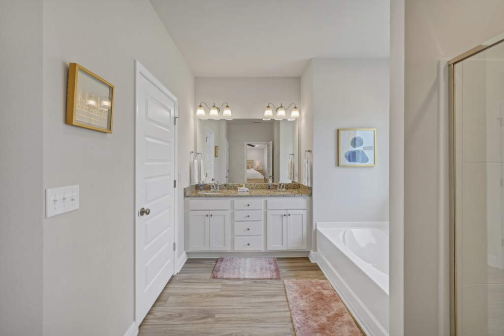 Double vanities and private water closet elevate the space for maximum utility