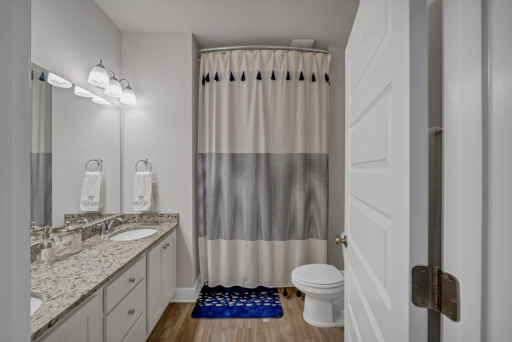 The guest bath offers a shower/tub combination, double vanity, and blow dryer