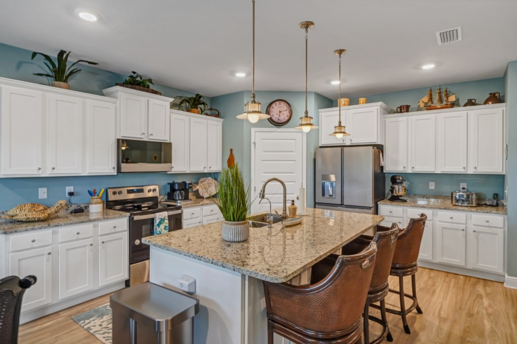 Modern kitchen with Café stainless appliances and stone countertops