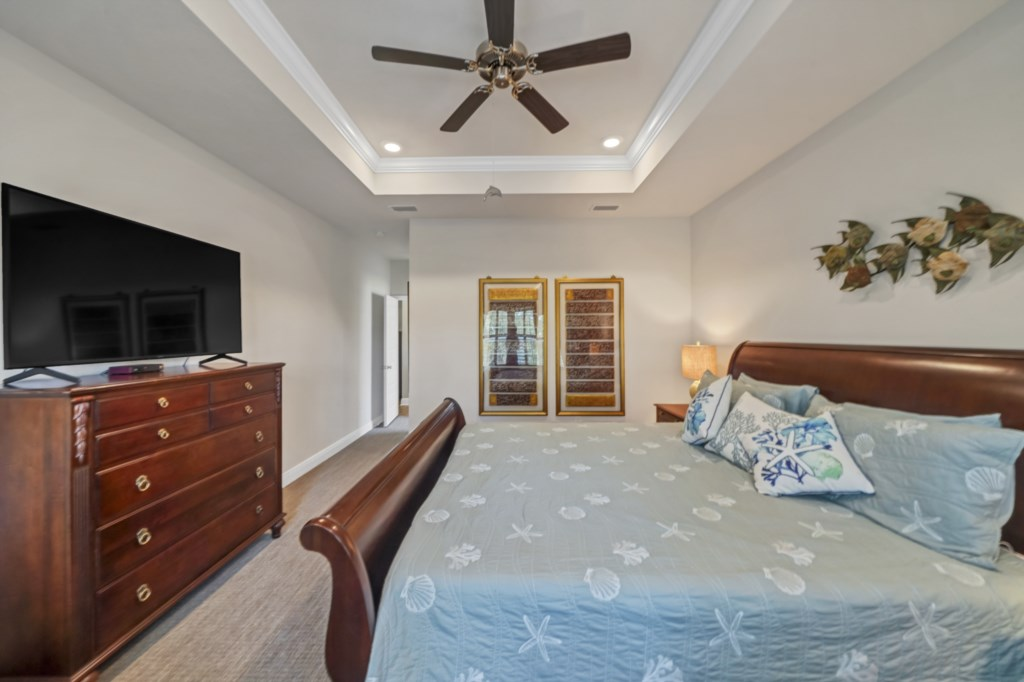 The primary bedroom offers a flat screen television, ceiling fan, and attached bathroom